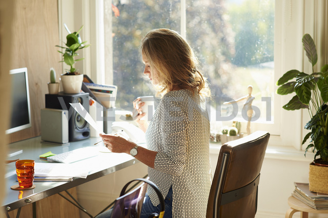 Woman drinking coffee and reading paperwork at desk in sunny home office - CAIF09015