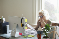 Young woman drinking tea and reading paperwork at desk in home office - CAIF09018