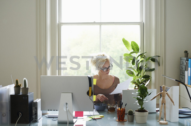 Young woman reading paperwork at desk in home office - CAIF09021