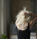Young woman with hands in hair revealing back tattoos - CAIF09027