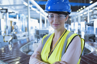 Portrait confident female worker with hard-hat and protective eyewear in factory - CAIF09060