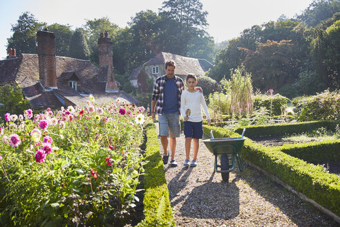 Father and son walking in sunny garden - CAIF09102