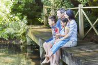 Family sitting at the edge of dock - CAIF09129