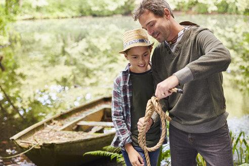 Father teaching son how to tie a rope knot - CAIF09168