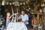 Father and daughter painting chair in workshop - CAIF09210
