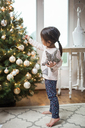 Toddler girl decorating Christmas tree - CAIF09228