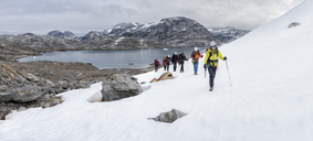 Greenland, Sermersooq, Kulusuk, Schweizerland Alps, group of people walking in snow - ALRF00928