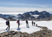 Greenland, Sermersooq, Kulusuk, Schweizerland Alps, group of people walking in snow - ALRF00934