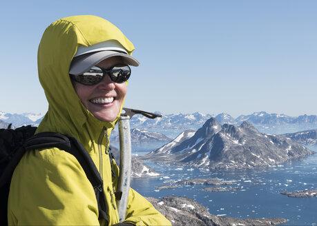 Greenland, Sermersooq, Kulusuk, Schweizerland Alps, portrait of happy mountaineer on summit - ALRF00943