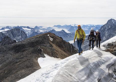 Greenland, Sermersooq, Kulusuk, Schweizerland Alps, mountaineers walking in snowy mountainscape - ALRF00949