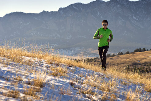 Man jogging on field against mountains - CAVF04129