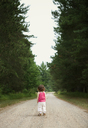 Rear view of girl standing on dirt road - CAVF04246