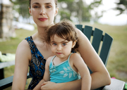 Portrait of mother and daughter sitting on chair - CAVF04249