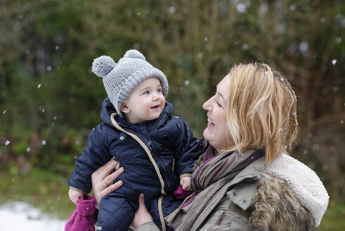 Baby girl on arms of her mother watching snowflakes for the first time - LBF01841