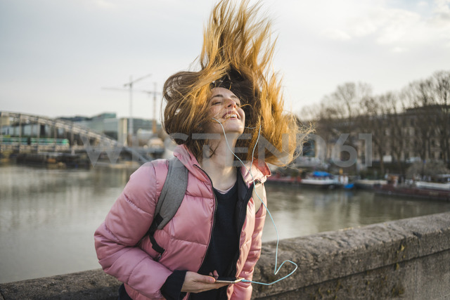 Paris, France, happy young woman listening music with earphones and smartphone tossing her hair - AFVF00288