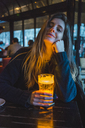 Paris, France, portrait of smiling young woman with glass of beer in a pub in the evening - AFVF00294