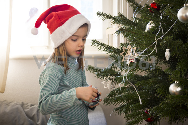 Little girl wearing Christmas cap decorating Christmas tree - LVF06775