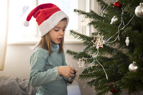 Little girl wearing Christmas cap decorating Christmas tree - LVF06775