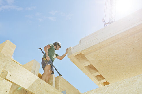 Austria, worker against the sun, positioning roof construction - CVF00271