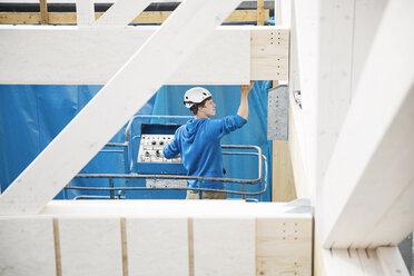 Austria, worker on hoist, positioning roof construction - CVF00277