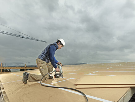 Austria, construction worker fixing medium-density fibreboard - CVF00280