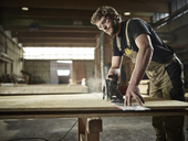 Carpenter sawing wood with handsaw - CVF00292