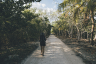 Cuba, Cienaga de Zapata, Young woman with backpack walking on tree-lined street - GUSF00532