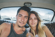 Cuba, Yound couple sitting in a vintage car, taking a selfie - GUSF00547