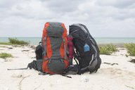 Cuba, Puerto Padre, Bahia de Malagueta, Two abandoned rucksacks on the beach - GUSF00550