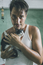 Young man holding little kitten, portrait - GUSF00556