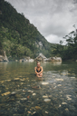 Cuba, Baracoa, Young woman sitting in Yumuri river - GUSF00559
