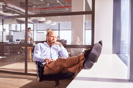 Pensive businessman sitting with feet up looking through sunny window in office - CAIF09295