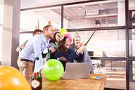 Playful business people celebrating birthday taking selfie with selfie stick in conference room - CAIF09298