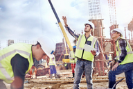 Construction workers talking at construction site - CAIF09301