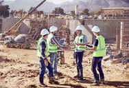 Construction workers and engineers shaking hands, meeting at sunny construction site - CAIF09313
