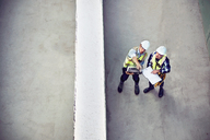 Construction worker and engineer with laptop talking at construction site - CAIF09316