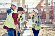 Female foreman talking to construction workers at sunny construction site - CAIF09325