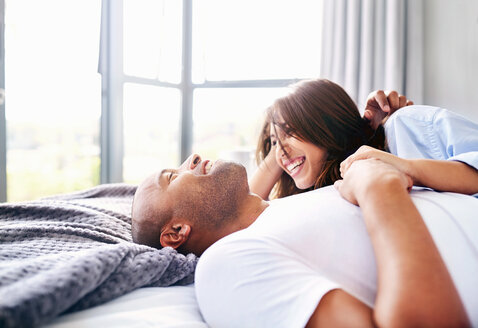 Smiling couple laying and cuddling on bed - CAIF09331