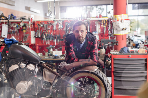 Portrait serious, confident motorcycle mechanic in workshop - CAIF09343