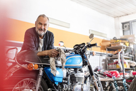 Portrait confident senior male motorcycle mechanic leaning on motorcycle in workshop - CAIF09358