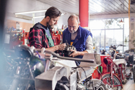Male motorcycle mechanics repairing part in workshop - CAIF09367