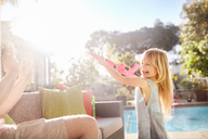 Playful daughter with squirt gun spraying father on sunny summer patio - CAIF09373