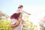 Father carrying daughter with bubble wand on shoulders in sunny summer park - CAIF09379