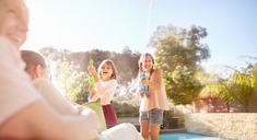 Playful sisters with squirt guns spraying water at sunny summer poolside - CAIF09382