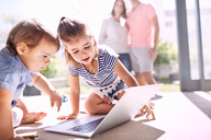 Brother and sister using laptop on sunny floor - CAIF09391