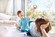 Mother watching son playing with bubble wand in sunny living room - CAIF09397