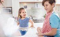 Sister throwing flower at brother, baking in kitchen - CAIF09400