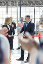 Business people cutting ribbon at new construction site ceremony - CAIF09403