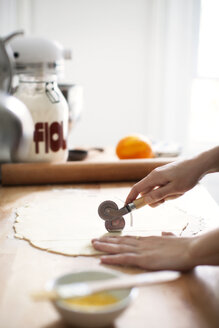 Cropped image of woman cutting pastry dough through cutter for preparing pie - CAVF04441