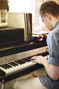 Side view of man playing piano at home - CAVF04501